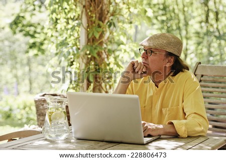 Senior man sits outdoors at a wooden table under an arbor and works on a laptop computer away from the office. It's summer and there's a background of green trees and bushes.  - stock photo