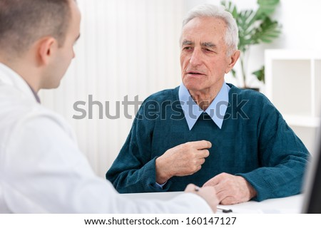 Senior man sits with his doctor and he complained of chest pain - stock photo