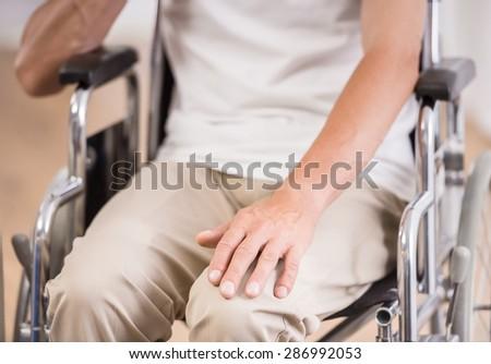 Senior man sitting in wheelchair at home. - stock photo