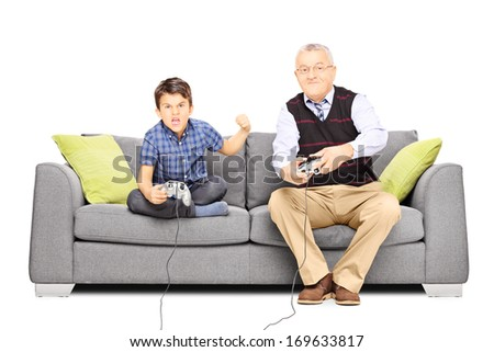 Senior man sitting on a couch and playing video games with his nephew, isolated on white background - stock photo