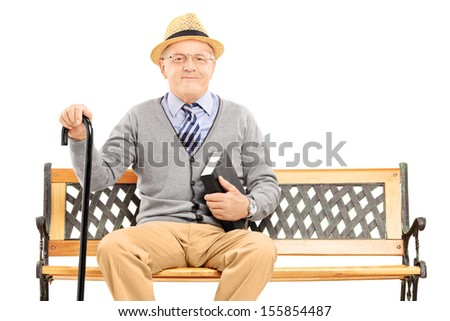 Senior man sitting on a wooden bench with book and looking at camera isolated on white background - stock photo