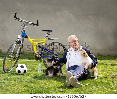 Senior man sitting on grass with dogs after bike ride - stock photo