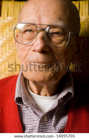Senior Man Sitting pleasant look on face.  Close Up. - stock photo