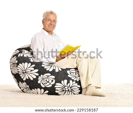 Senior man sitting with a book in armchair on white background - stock photo