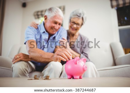 Senior man sitting with woman on sofa and putting coins in piggy bank - stock photo