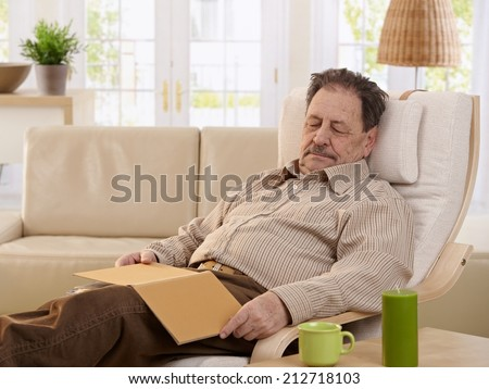 Senior man sleeping in armchair at home. - stock photo