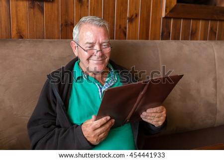 Senior man smiling big and reading a restaurant menu ready to order food - stock photo