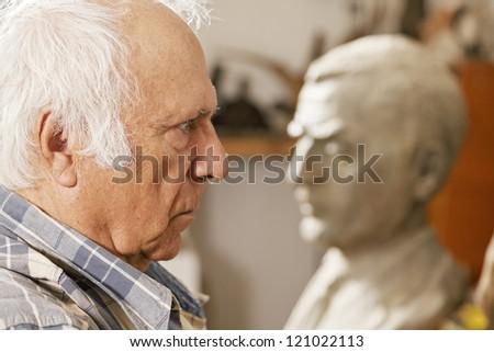 Senior man standing against statue profile view closeup photo - stock photo