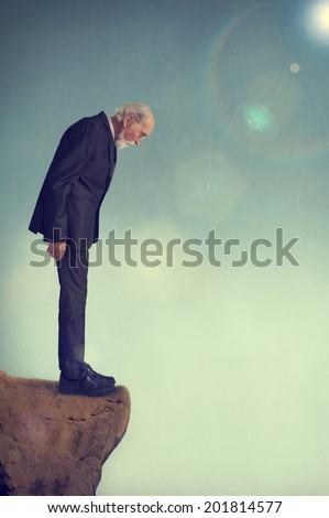 senior man standing alone on a cliff ledge - stock photo