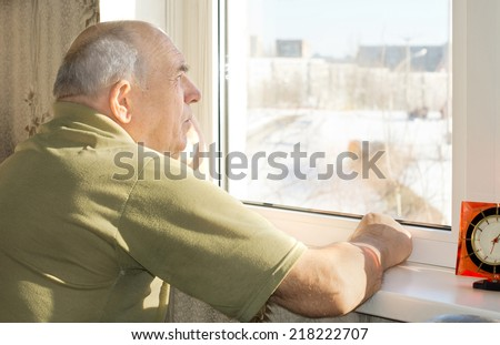 Senior man standing reminiscing as he stares out of a window with a faraway expression as he recalls nostalgic old memories - stock photo