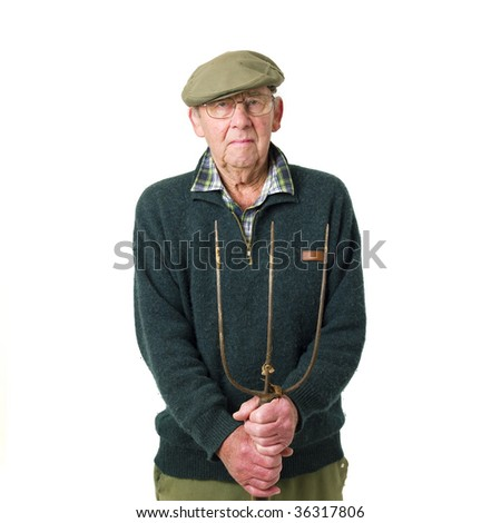 Senior man standing with pitch fork - stock photo