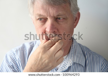 senior man strokes his mustache - stock photo
