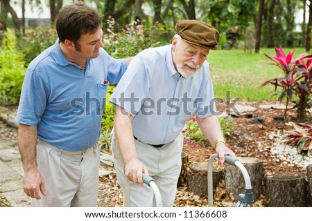 Senior man struggling to us a walker.  His adult son is helping him. - stock photo