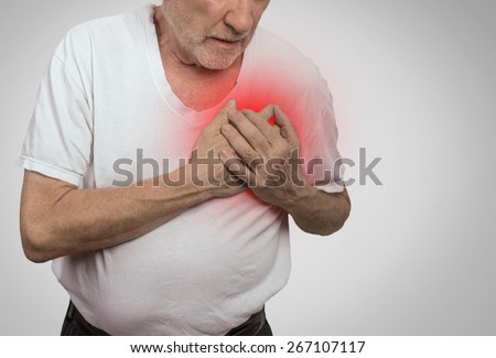 senior man suffering from bad pain in his chest isolated on gray background  - stock photo