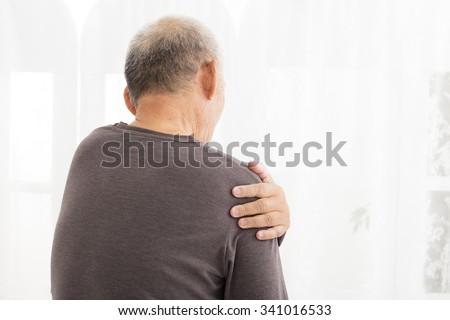 senior man suffering in shoulder pain - stock photo