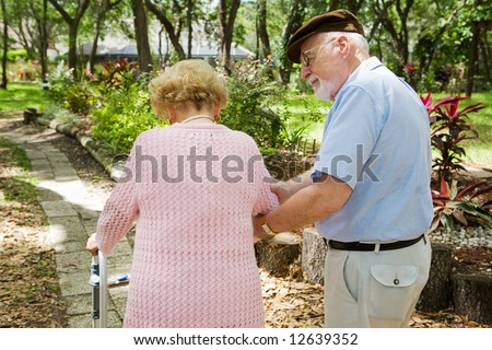 Senior man taking care of his disabled wife. - stock photo