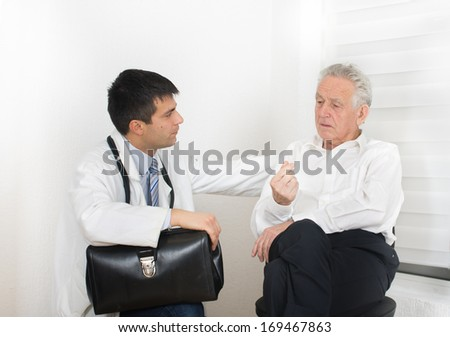 Senior man talking about symptoms to young male doctor - stock photo