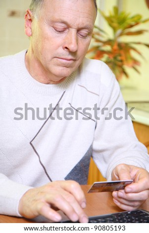 Senior man using credit card to shop at home - stock photo