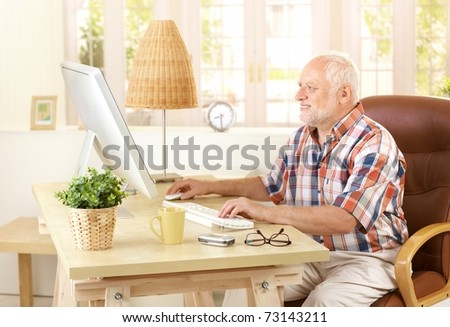 Senior man using desktop computer at home, looking at screen, smiling.? - stock photo