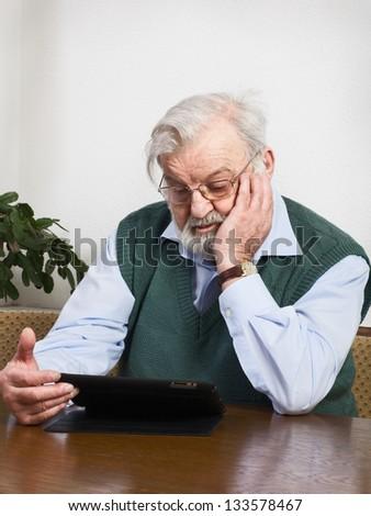 Senior man using digital tablet - stock photo