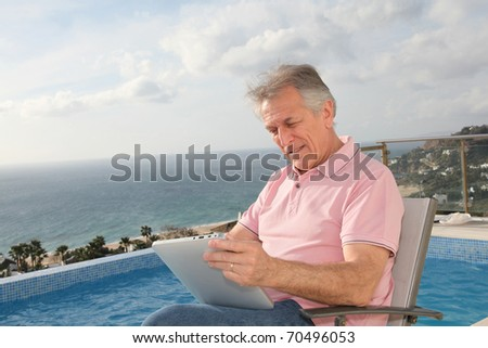 Senior man using electronic tablet by a swimming-pool - stock photo