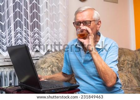 Senior man using laptop and drinking whiskey at home. - stock photo