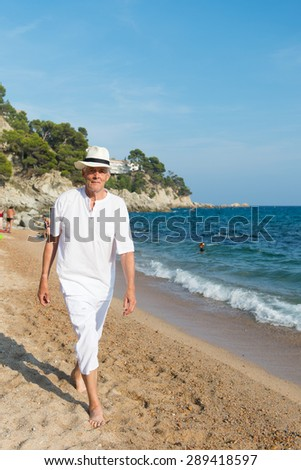 Senior man walking at the beach in white suit - stock photo