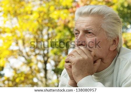 Senior man walking in the park in autumn - stock photo