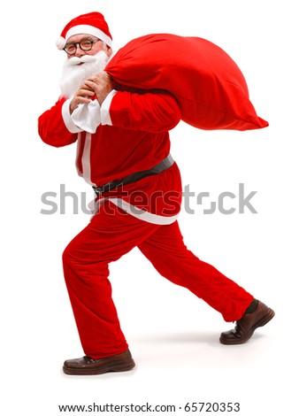 Senior man wearing Santa Claus uniform, walking with full bag - stock photo