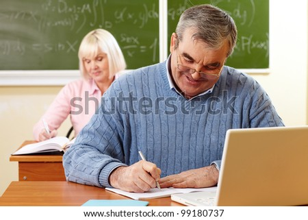Senior man with a cheerful smile doing the task in classroom - stock photo