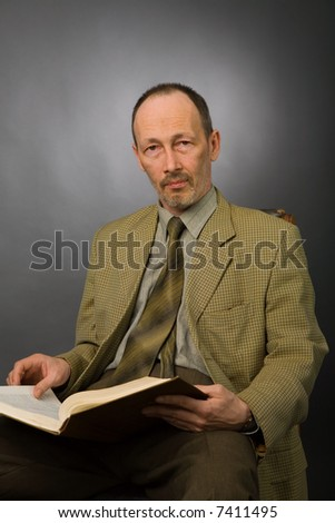 senior man with book on gray background - stock photo
