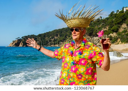 Senior man with cocktail drink at the tropical beach - stock photo