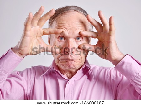 Senior man with hands on eyes on grey background - stock photo
