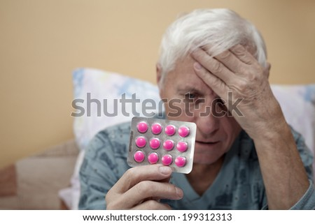 Senior man with headache holding painkillers. - stock photo