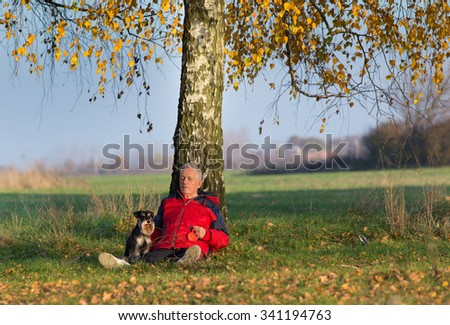 Senior man with his dog Miniature schnauzer sitting on the ground and leaning on the tree in the park - stock photo