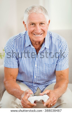 Senior man with joystick looking at camera and smiling in living room - stock photo