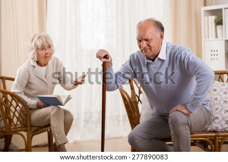 Senior man with knee arthritis and caring wife - stock photo
