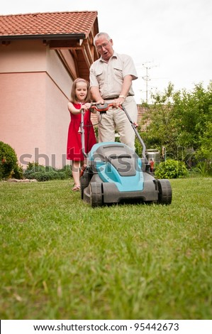 Senior man with lawn mower and child - stock photo