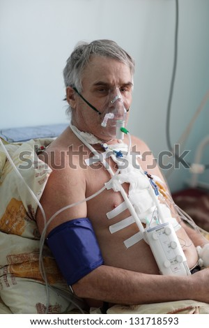 Senior man with oxygen mask in a hospital ward - stock photo