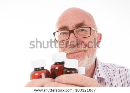 Senior man with pill bottles - stock photo