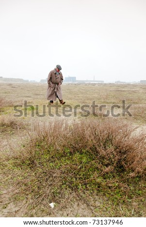 Senior man with raincoat and hat walking on sand with grass. Open space. Lost. - stock photo