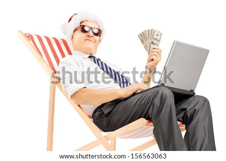Senior man with santa hat seated on a beach chair holding banknotes and working on a laptop isolated on white background - stock photo