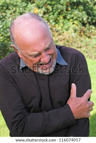 Senior man with severe pain in his left arm - stock photo