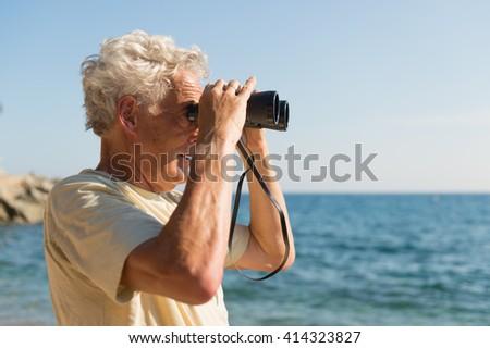 Senior man with spy glasses at the beach - stock photo