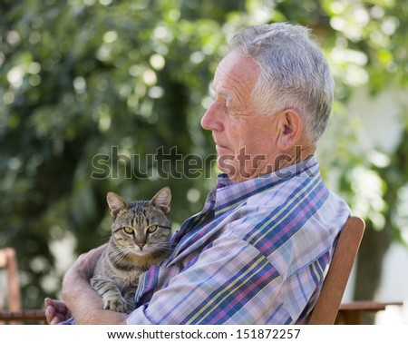 Senior man with tabby cat in his garden - stock photo