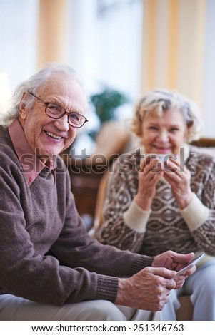 Senior man with touchpad looking at camera while resting at home on weekend - stock photo
