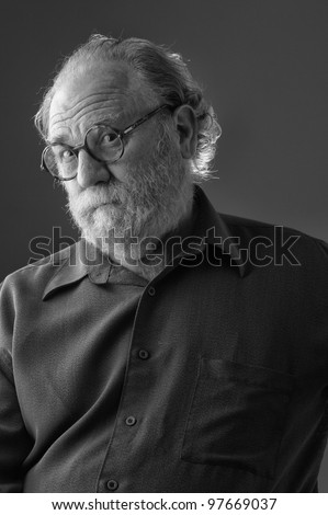 Senior man with white beard and round glasses tilts head back and raises eyebrows. Vertical layout with copy space. - stock photo