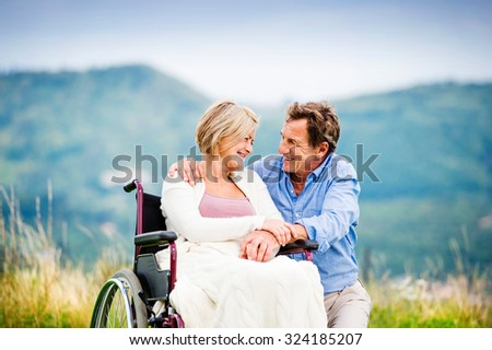 Senior man with woman in wheelchair outside in nature - stock photo