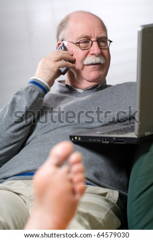 Senior man working on laptop and calling by phone - stock photo