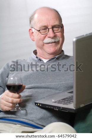 Senior man working on laptop with a glass of wine - stock photo